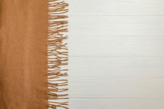 Осенний фон с шерстяным теплым шарфом бежевого цвета. Premium Фотографии