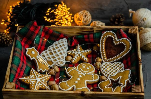 暗い背景に描かれた白い粉砂糖とクリスマスのジンジャーブレッド。 Premium写真
