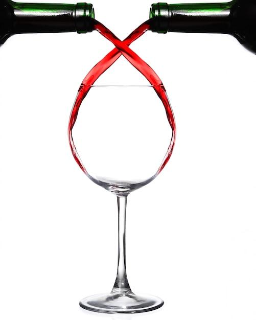 Две бутылки наливают красное вино в один стакан Premium Фотографии