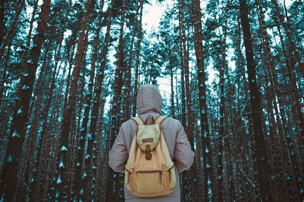 雪に覆われた冬の森に立っている若い男 Premium写真