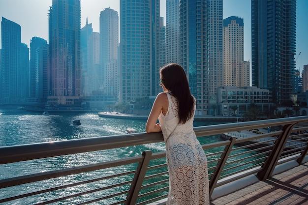 ドバイマリーナで幸せな美しい観光女性 Premium写真