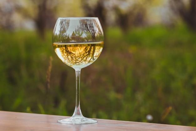 開花のリンゴ園で白ワインとワイングラス Premium写真
