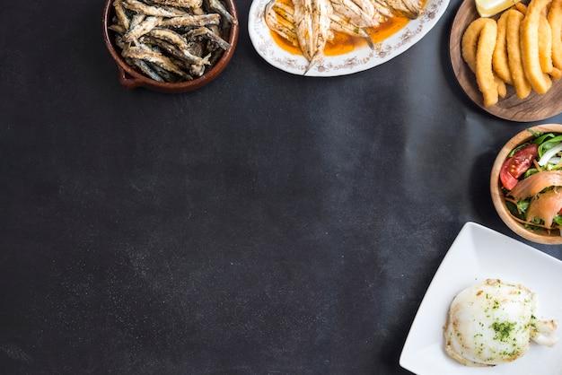 Смешанная рыба (каракатицы, сардины, жареные, салат с лососем) на черном фоне Premium Фотографии