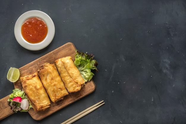 Жареные овощные блинчики с начинкой из свежих ингредиентов и кислого соуса в восточном ресторане Premium Фотографии