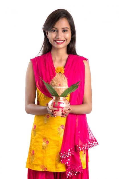 ヒンドゥー教のプージャに不可欠な伝統的な銅カラッシュ、インドの祭り、ココナッツと花の装飾とマンゴーの葉と銅カラッシュを保持しているインドの少女。 Premium写真