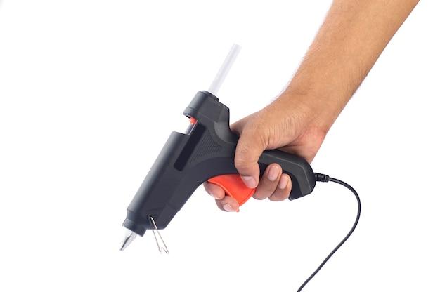 Рука держит электрический пистолет горячего клея Premium Фотографии