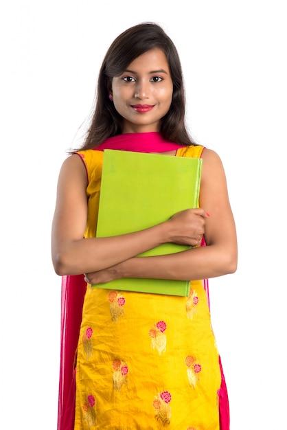 Хорошенькая молодая девушка держит книгу и позирует на белой поверхности Premium Фотографии