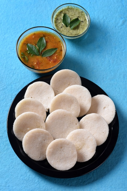 青い表面にサンバーとココナッツのチャツネが入ったイドリ、インド料理:南インドのお気に入りの料理ラヴァイドゥリまたはセモリナイドゥルまたはラヴァイドゥイ、サンバーとグリーンココナッツのチャツネ添え。 Premium写真