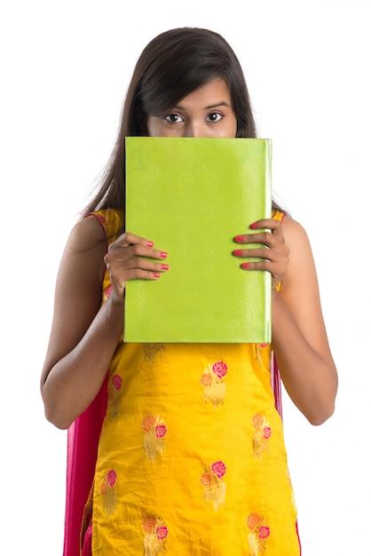 Милая молодая женщина держа книгу и представляя на белизне Premium Фотографии