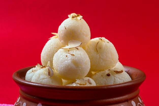 インドの甘いまたはデザート-ラスガラ、赤のナプキンで粘土ボウルで有名なベンガル語の甘い Premium写真