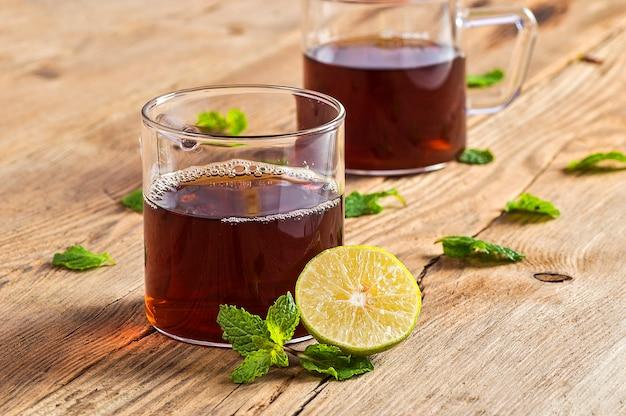 ジンジャー、レモン、ミントの木製テーブルの上のお茶 Premium写真