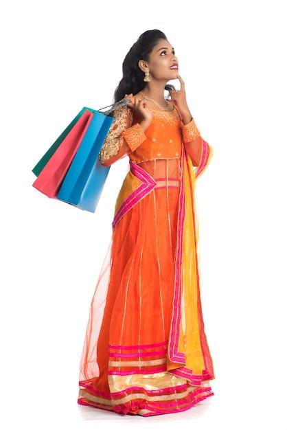 伝統的な民族衣装を着て買い物袋を保持している美しいインドの若い女性。白い壁に分離 Premium写真
