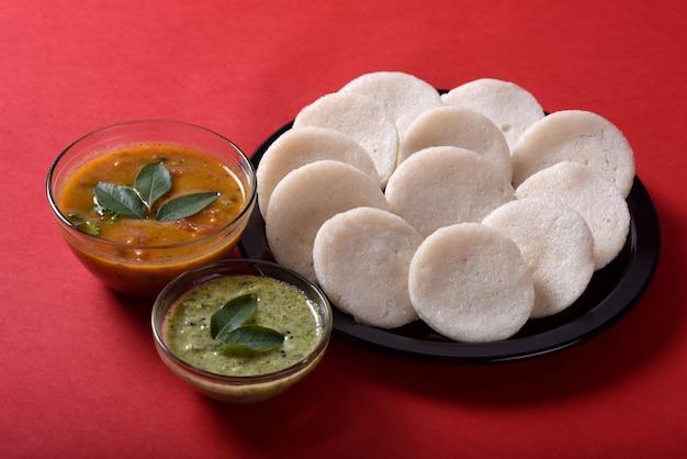 サンバーとココナッツのチャツネを添えたイドゥリ、インド料理:サンバーとグリーンチャツネを添えて、インド南部のお気に入りの食べ物、ラヴァイドゥリまたはセモリナイヴォリまたはラヴァイドゥイ。 Premium写真