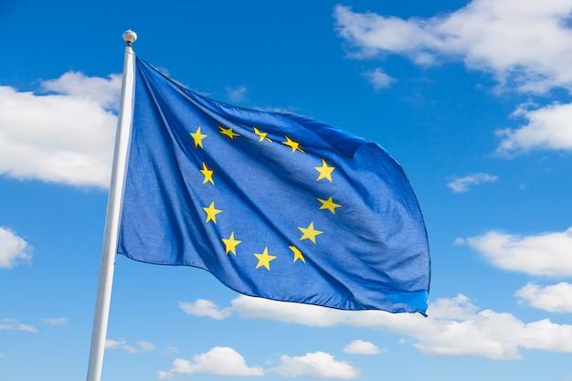 Размахивая флагом европейского союза на фоне голубого неба. Premium Фотографии
