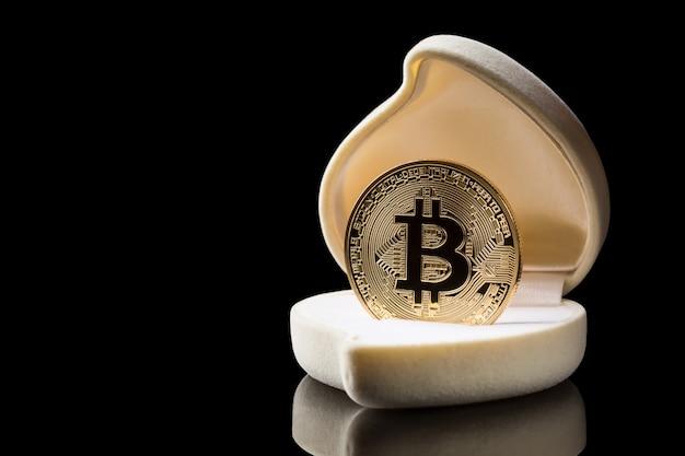 反射と黒の背景に分離された結婚指輪ボックスに黄金のビットコインコイン Premium写真