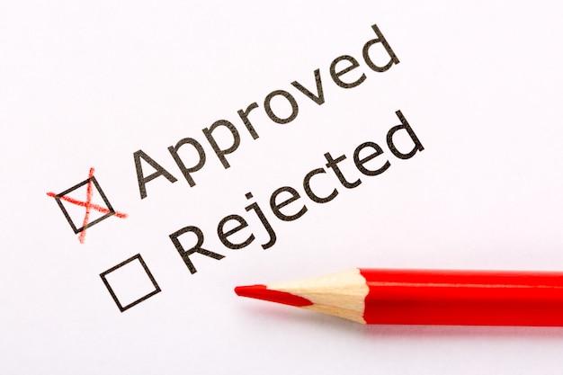 白い紙に赤鉛筆で承認または拒否されたチェックボックスを閉じます。 Premium写真