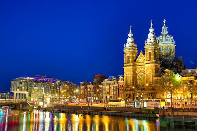 夕暮れ、オランダのアムステルダムの運河と聖ニコラス教会 Premium写真