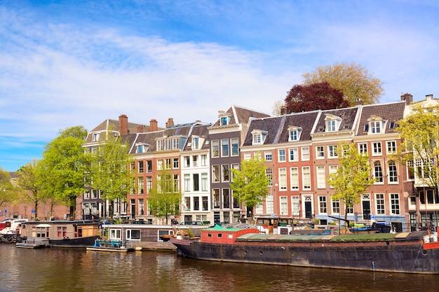 Городской вид на канал амстердама летом с голубым небом, дома лодки и традиционные старые дома Premium Фотографии