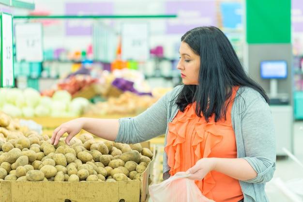 スーパーマーケットの店でジャガイモを選ぶ女性。 Premium写真