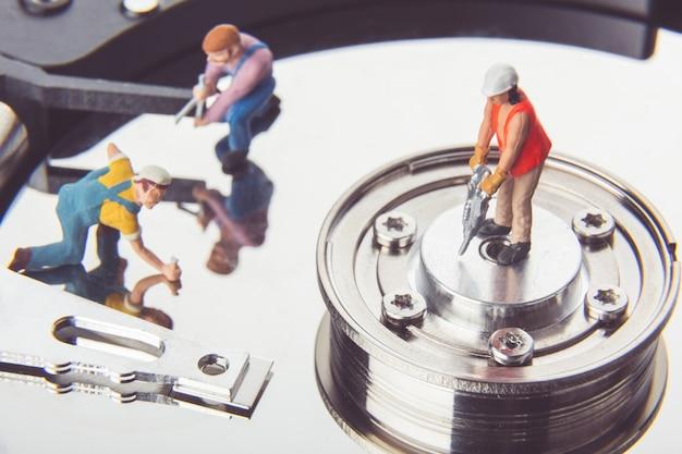 ハードディスクドライブを修理する技術者の労働者。 Premium写真
