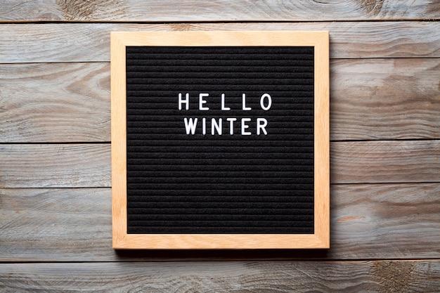 こんにちは木製の背景に文字ボード上の冬の言葉 Premium写真