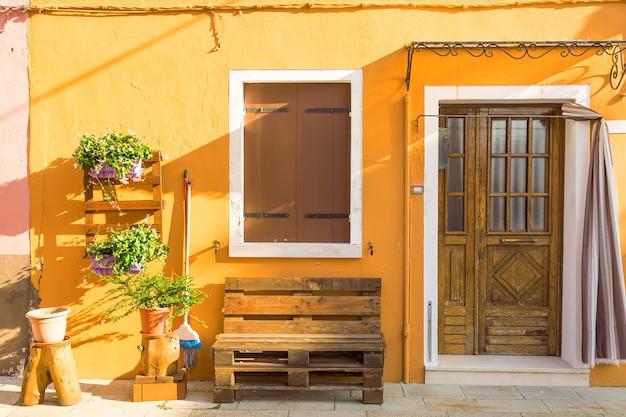Желтый дом с цветами и скамейкой, разноцветные дома на острове бурано возле венеции, италия, Premium Фотографии