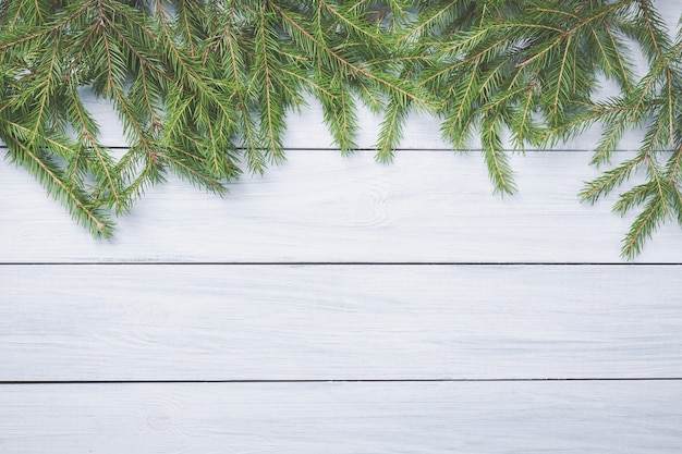 Рождественская елка ветви на вершине белой деревянной доске. Premium Фотографии