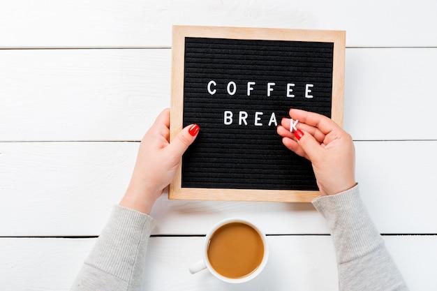 Женские руки с красными гвоздями, держащие доску для писем с перерывом на кофе слов около чашки кофе по белому деревянному столу. вид сверху Premium Фотографии