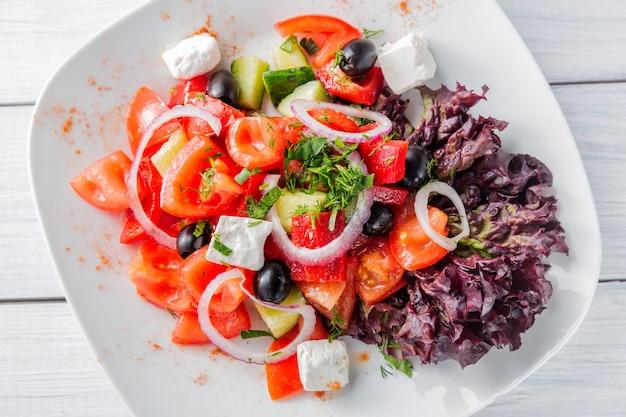 白い皿と木製のテーブルに玉ねぎの新鮮なギリシャ風サラダ Premium写真