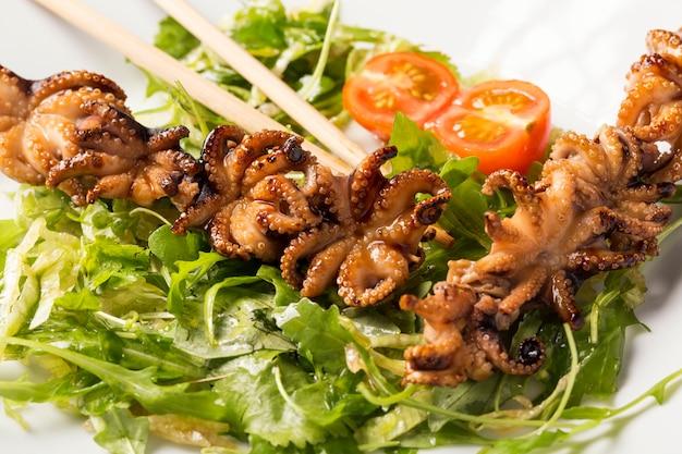 Барбекю младенца осьминога на белой тарелке с травами, помидорами и палочками Premium Фотографии