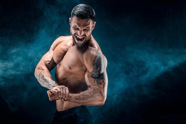 ハンサムなパワー運動男ボディービルダー。暗い煙の壁にフィットネス筋肉ボディ。 。 Premium写真