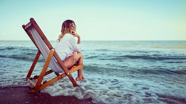 Красивая женщина, отдыхая на пляже лежак Premium Фотографии