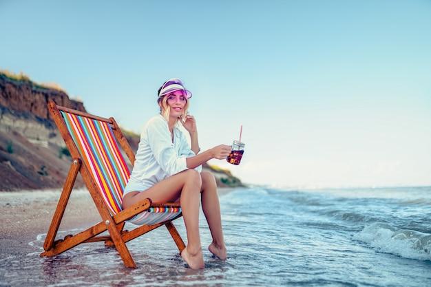 Красивая женщина, отдыхая на пляже лежак и пьет газированную воду Premium Фотографии