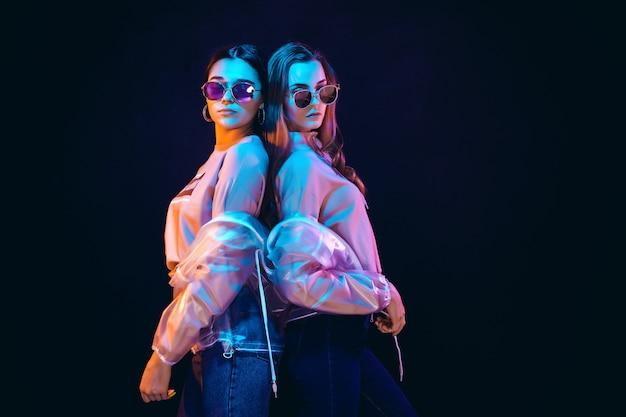 ネオンの光でポーズをとってスタイリッシュな若い女性 Premium写真