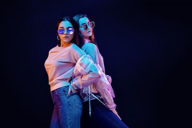 Стильные молодые женщины позируют в неоновом свете Premium Фотографии