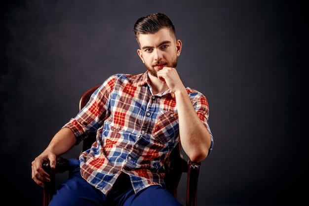 暗い背景上の長い髪のひげを生やした男性の肖像画。 Premium写真