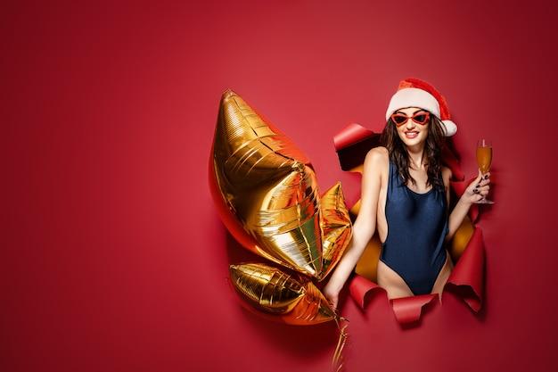 黄金の風船を保持しているサンタ帽子の女 Premium写真