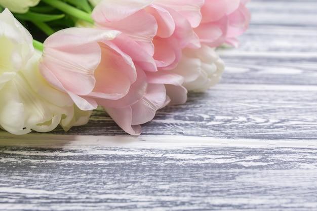 Розовые и белые очень нежные тюльпаны на белом, сером деревянном му Premium Фотографии