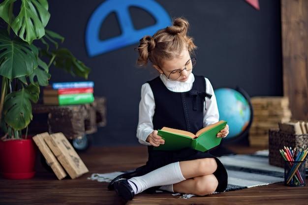 学校で教科書を読んでスマートな女の子 Premium写真