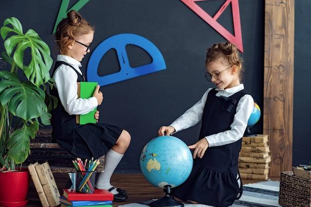 Умные девушки читают книги и изучают глобус в школе Premium Фотографии