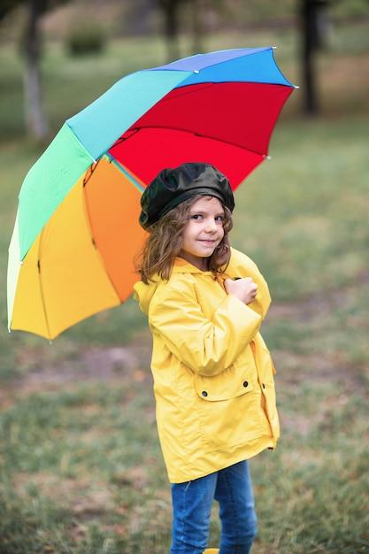Счастливая смешная детская девочка с зонтиком в резиновых сапогах Premium Фотографии