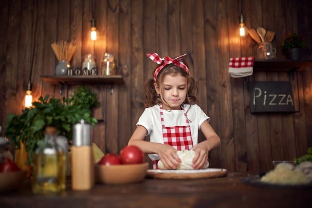 ピザのパン生地を混練市松模様のエプロンでかわいい女の子 Premium写真
