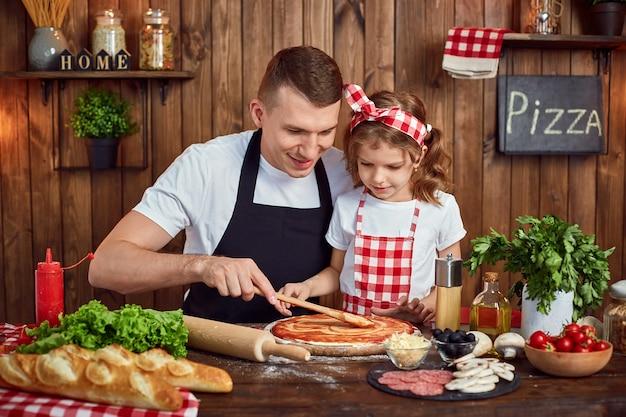 お父さんがピザを調理しながらソースを広めるのを助ける美しい娘 Premium写真