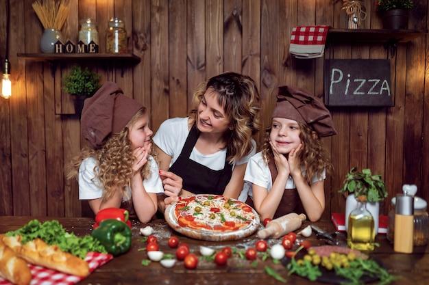 キッチンでピザを調理する娘を持つ母 Premium写真