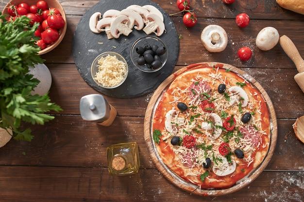 木の板に自家製ピザ、トマトとサラミ、マッシュルーム、古い木製のテーブル、トップビューでイタリアンスタイル Premium写真