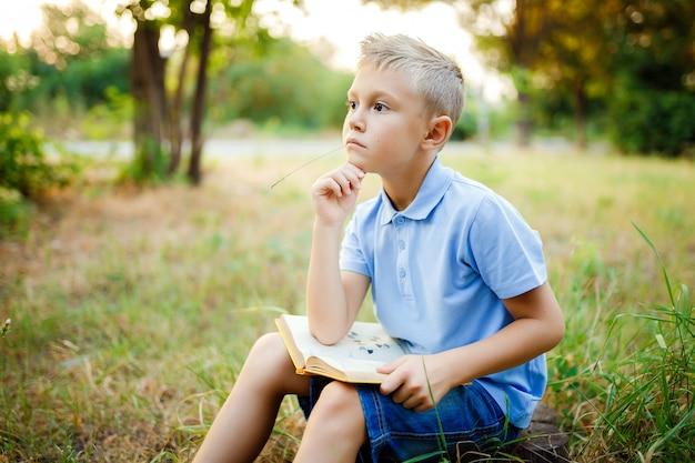 膝の上に本を持って森に座って目をそらす子供。 Premium写真