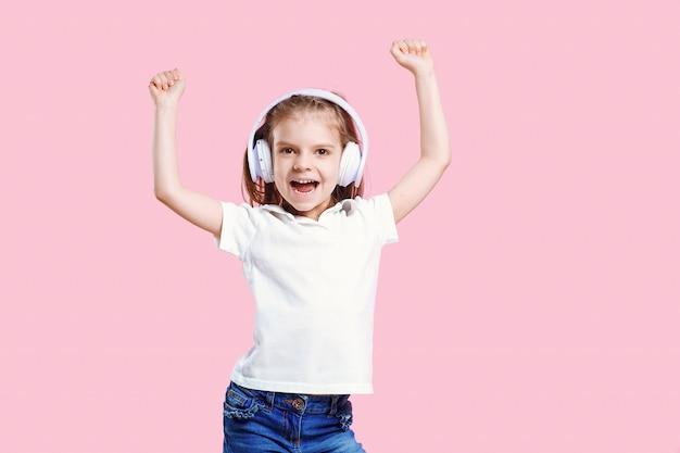ヘッドフォンで音楽を聴いている女の子。幸せなダンス音楽、目を閉じて、笑顔のポーズを楽しんでいるかわいい子 Premium写真