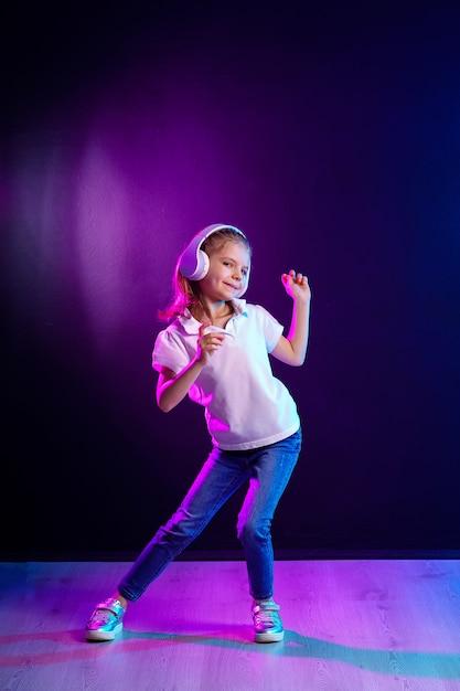 ヘッドフォンで音楽を聴いている女の子。踊る少女。音楽に合わせて踊る幸せな小さな女の子。幸せなダンス音楽を楽しんでいるかわいい子。 Premium写真
