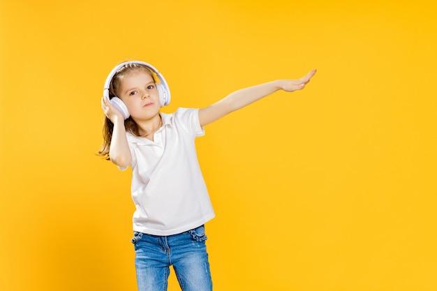 ワイヤレスヘッドフォンで音楽を聴いている女の子。踊る少女。音楽に合わせて踊る幸せな小さな女の子。幸せなダンス音楽を楽しんでいるかわいい子。 Premium写真