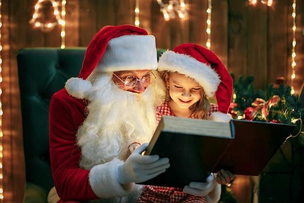 かわいい女の子にプレゼントを与えるサンタクロース Premium写真
